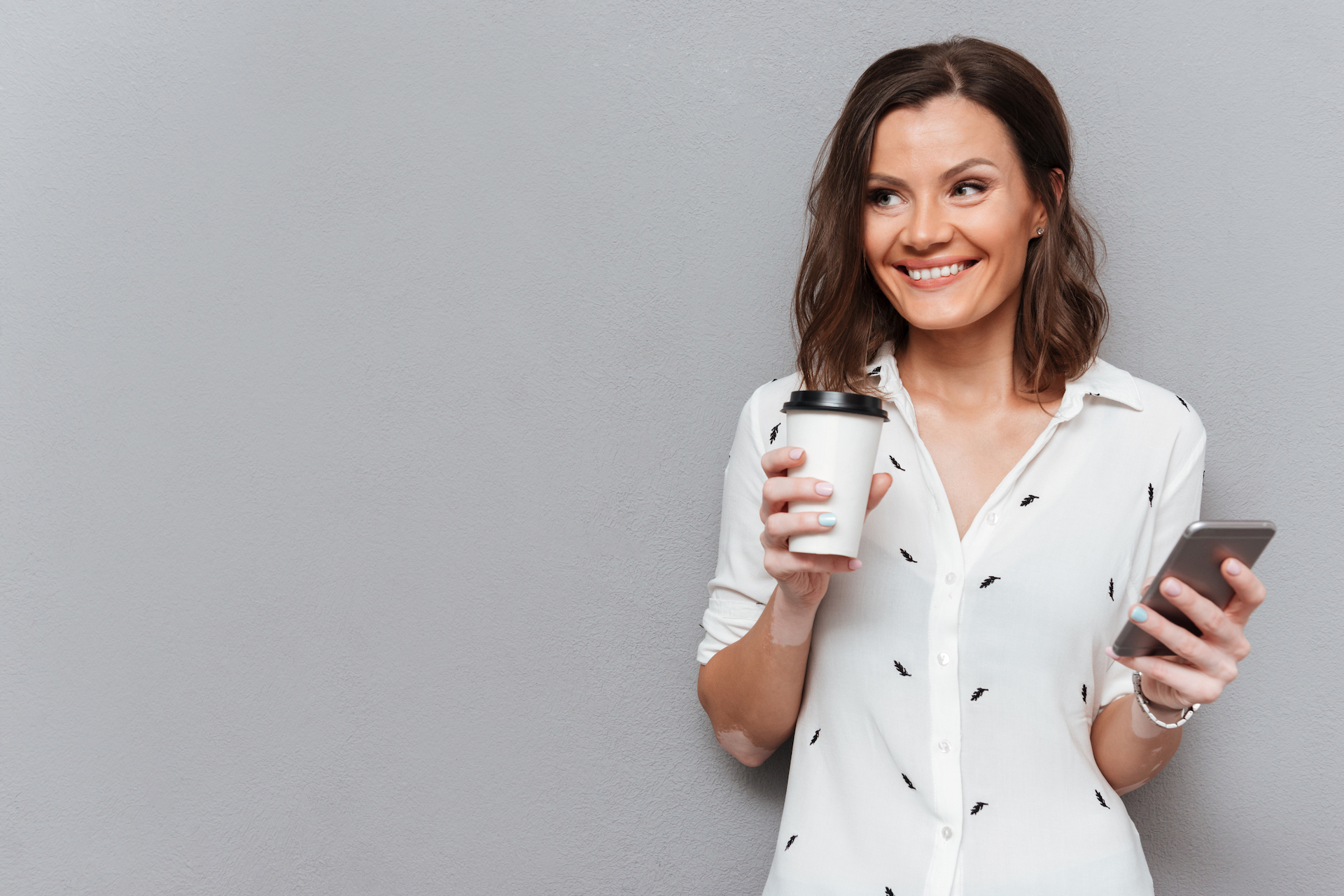 Glad woman with cup of coffee and smartphone in hands